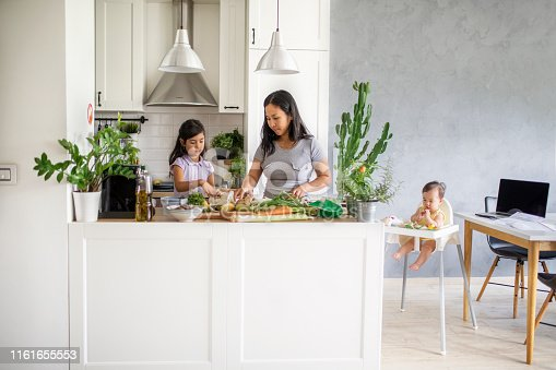 Asian mother with kids at home making healthy vegetables meal