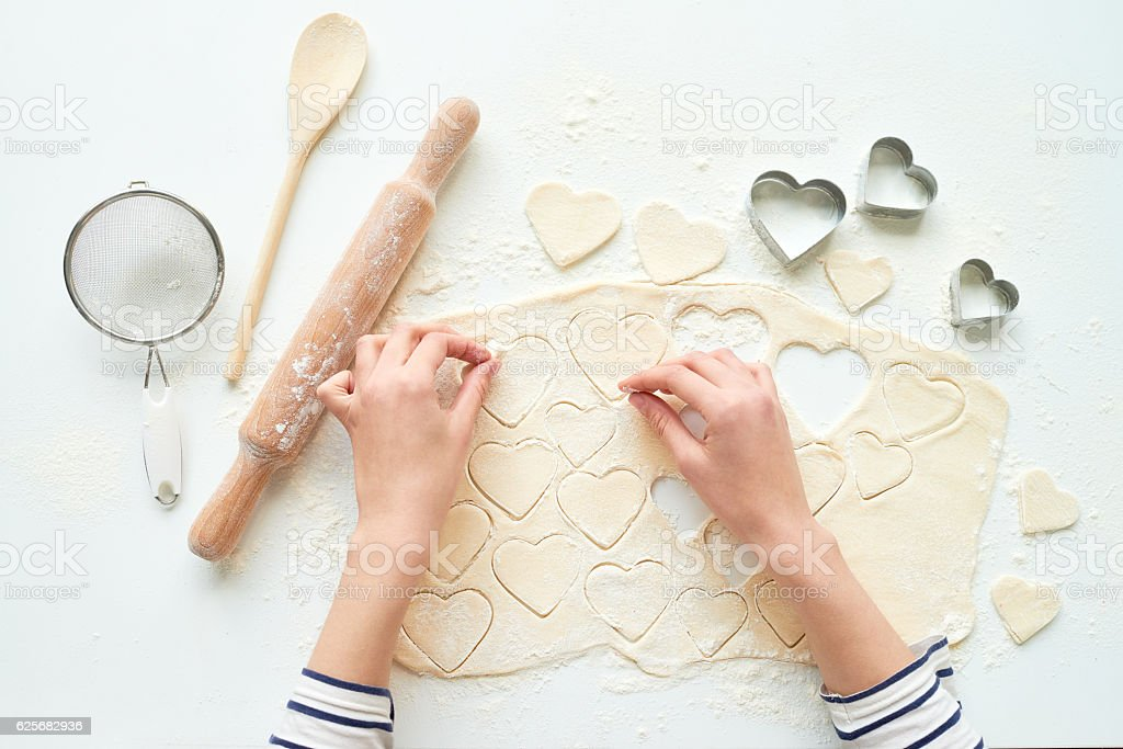 Making heart-shaped cookies stock photo