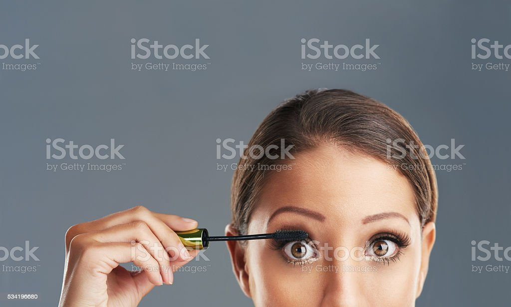 Making her eyes pop with mascara stock photo
