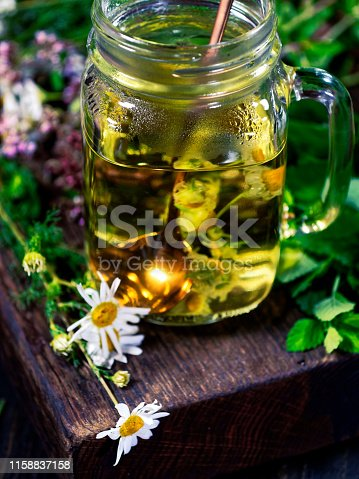 A cup of fresh camomile tea on the wooden table