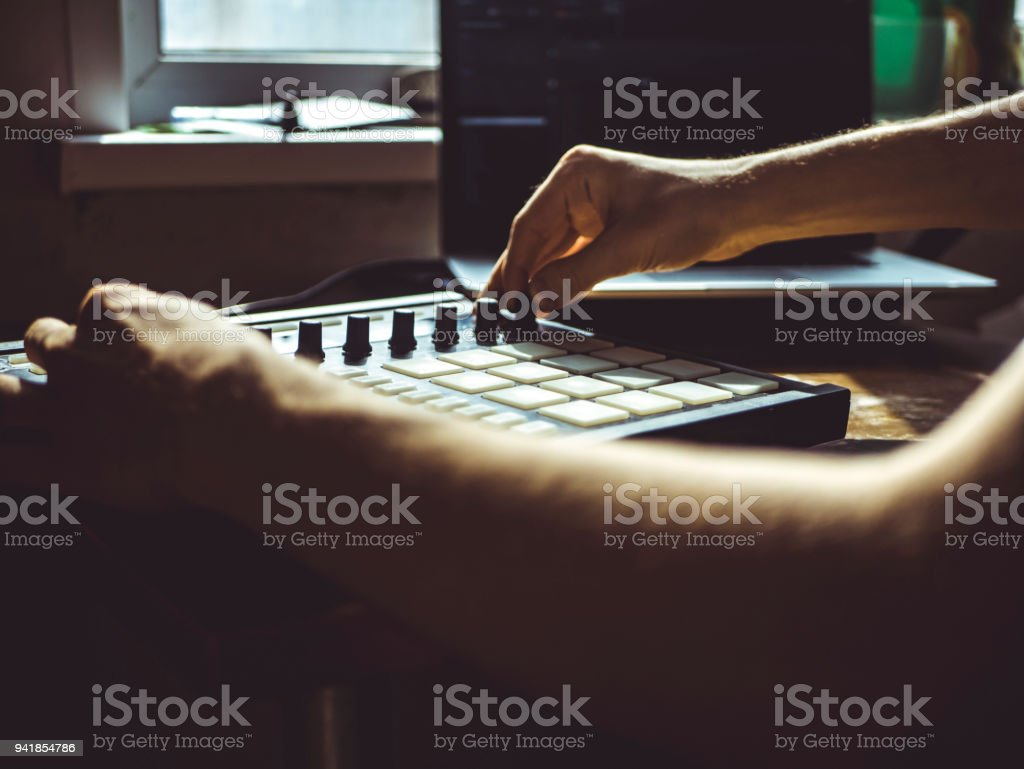 making hip hop beats on the drum machine controller at the home studio with laptop stock photo