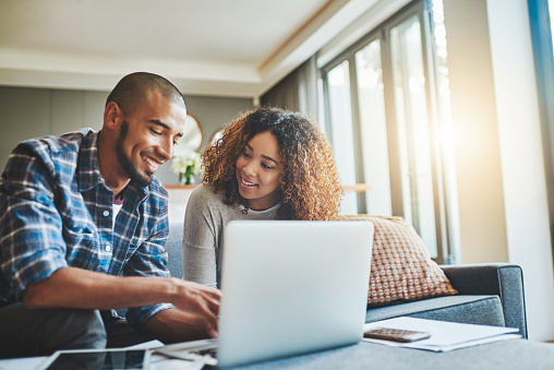 Shot of a young couple using a laptop while working on their home finances