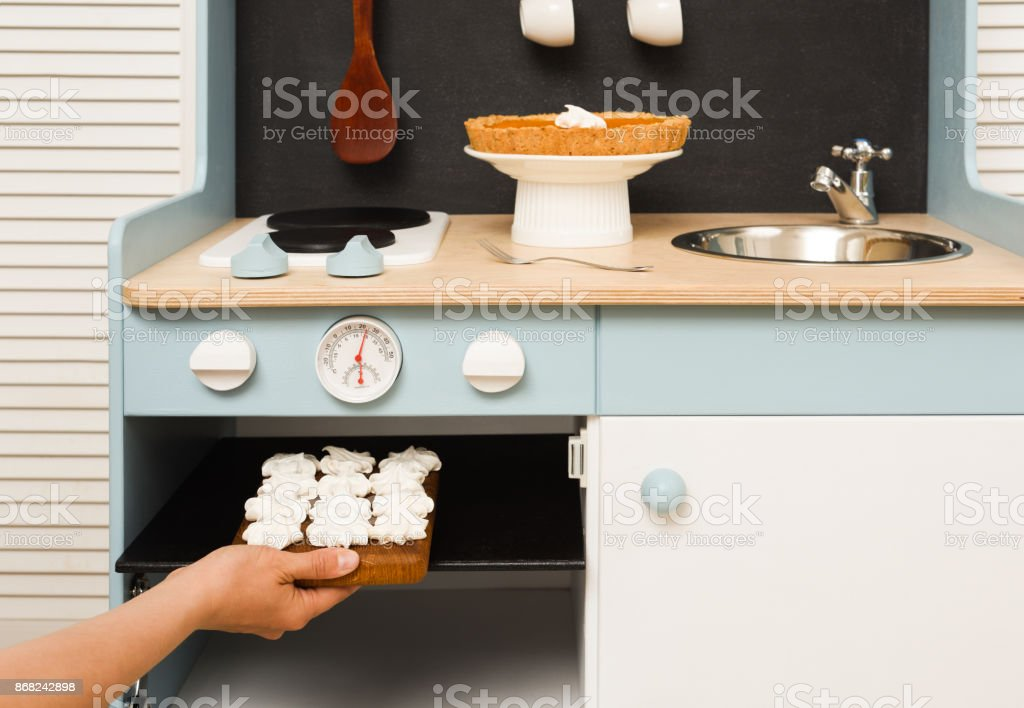 Making homemade desserts in toy kitchen. Meringues in stove and pumpkin pie on table stock photo