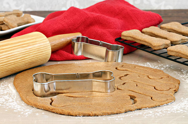 Making homemade dog biscuits Dog biscuit dough with rolling pin and bone shaped cookie cutters on a silicone mat. cookie cutter stock pictures, royalty-free photos & images