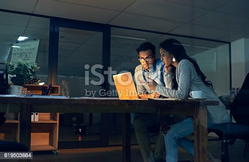 Cropped shot of two colleagues working late on a laptop in an office