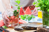 Person wearing linen apron making infused water with watermelon. Midsection view over the table