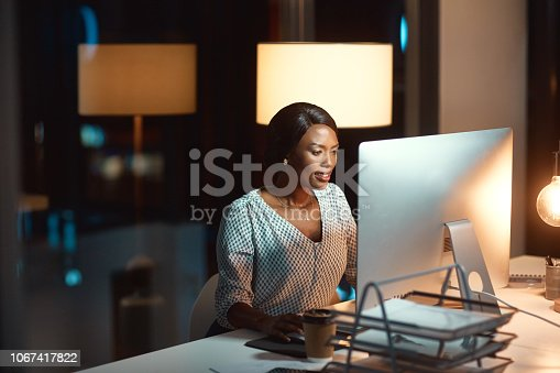 Shot of a young businesswoman using a computer during a late night at work