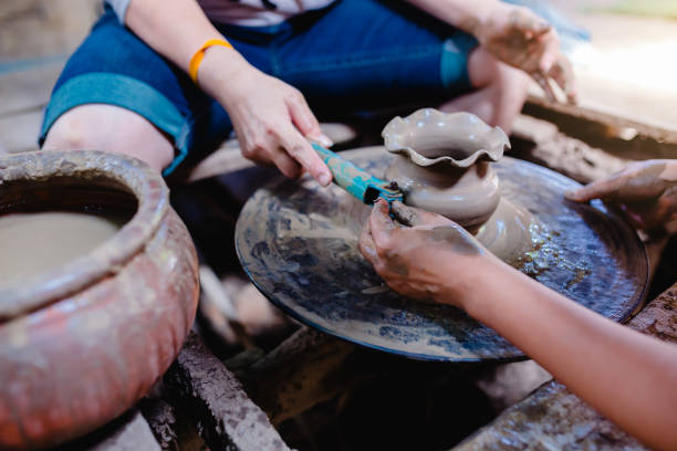 Making it together. close-up to hands of potter teacher and woman stock photo