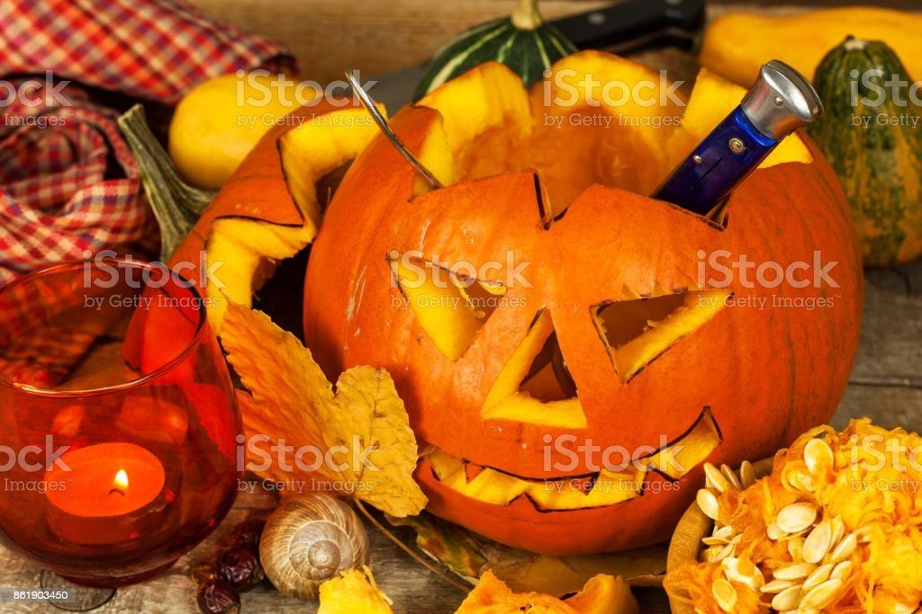 Making Jack o lantern. Carving the pumpkin. Hollowing out a scary pumpkin to prepare halloween lantern. Making Jack o lantern. Carving the pumpkin. Hollowing out a scary pumpkin to prepare halloween lantern Agriculture Stock Photo