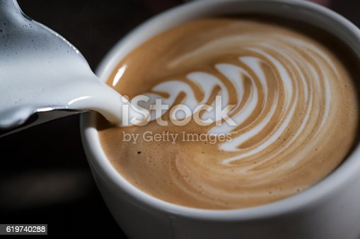 Making latte Art on a Cappucinno. Freshly made with cream