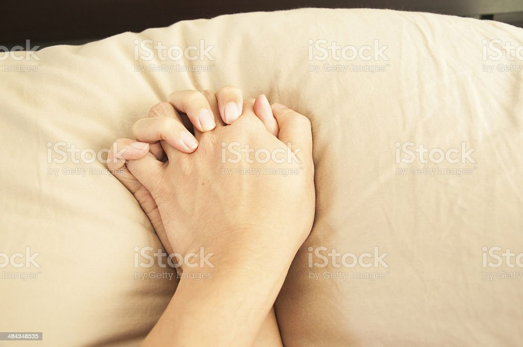 Making love in bed focus on hands stock photo