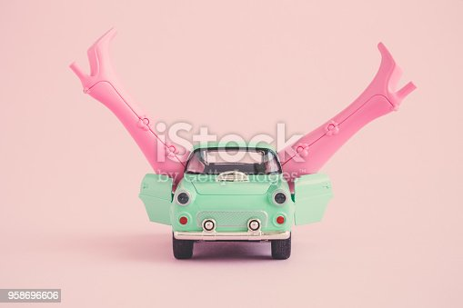 Miniature retro car with doll boots on pastel pink background. Sex in the car on first date minimal creative abstract concept.