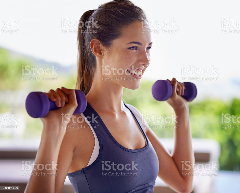 Making magic with her muscles Shot of an attractive young woman working out with weightshttp://195.154.178.81/DATA/i_collage/pi/shoots/783594.jpg 20-24 Years Stock Photo