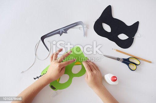 istock Making masks  paper  holiday Halloween Monster's  mask Black cat  Hands top view 1010378446