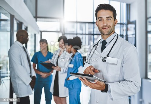 Portrait of a young doctor using a digital tablet in a hospital with his colleagues in the background