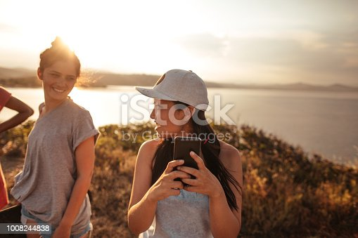 Young woman photographing with smart phone on the road trip