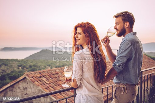 Young couple drinking wine on balcony at their holiday tourist resort. Enjoying in peciful summer holidays.