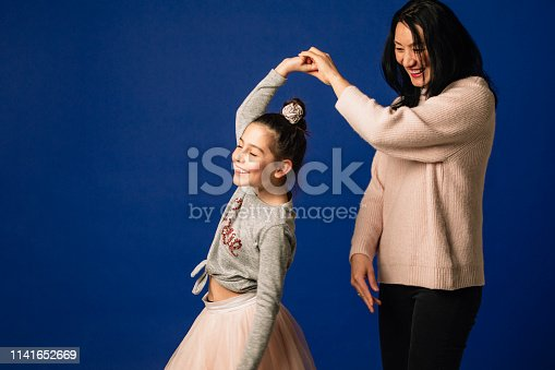 A mother and daughter dancing together and having fun in the studio.