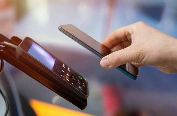 making mobile payments from pos device via mobile phone stock photo