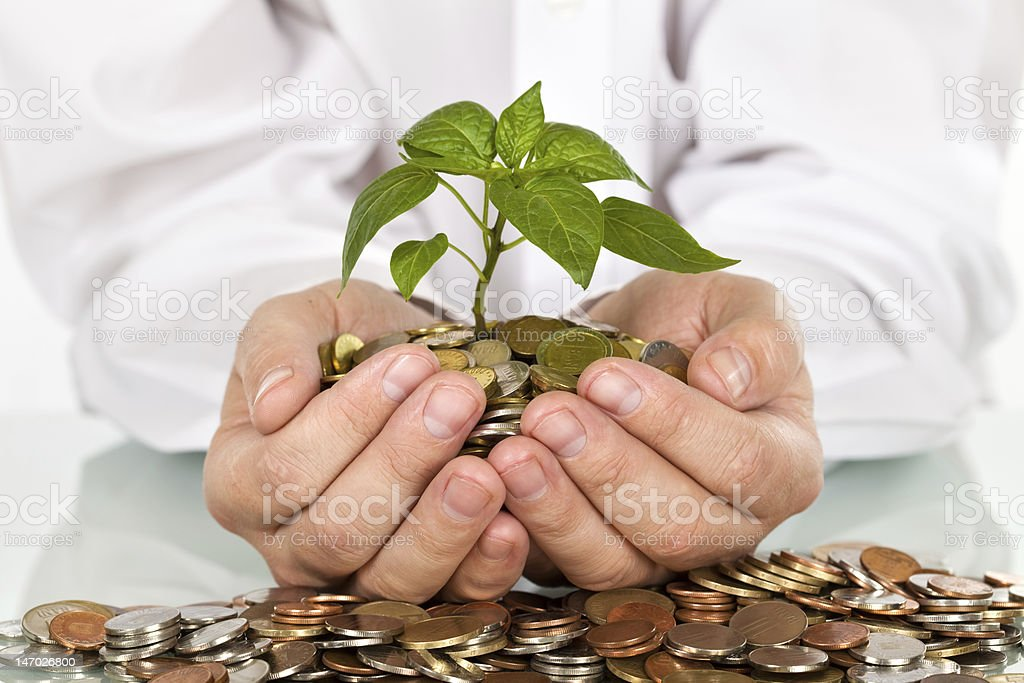 Making money and good investments concept Businessman holding plant sprouting from a handful of coins - good investment and money concept Banking Stock Photo
