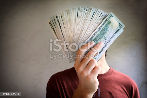 close up image of young male hands holding pile of money and covering his face