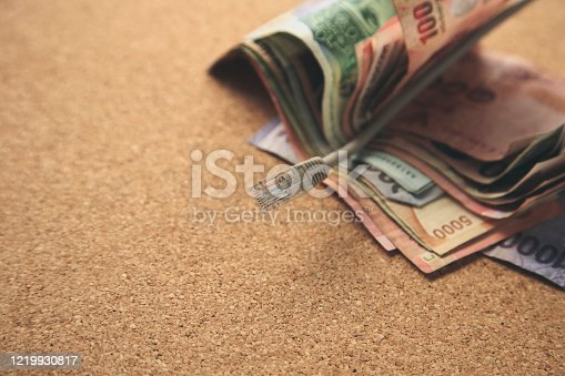 Making money online concept image consisting of human hand, cash and an internet cable.