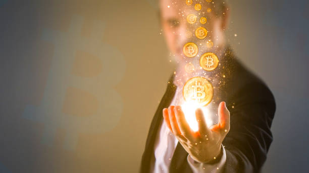making money with bitcoin - Bitcoins coming from business man's hand stock photo