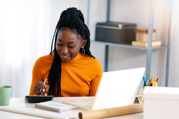 Making money work for her business Close up of one African American woman using calculator, calculating finance at home, female hands and paper document at table close up, economist or financier writing report, student doing homework refund stock pictures, royalty-free photos & images