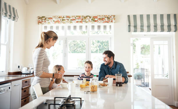 Making morning time family quality time Shot of a happy family of four having breakfast together in the kitchen at home breakfast stock pictures, royalty-free photos & images