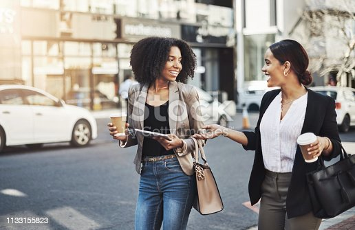 Shot of two businesswomen having a discussion while walking in the city