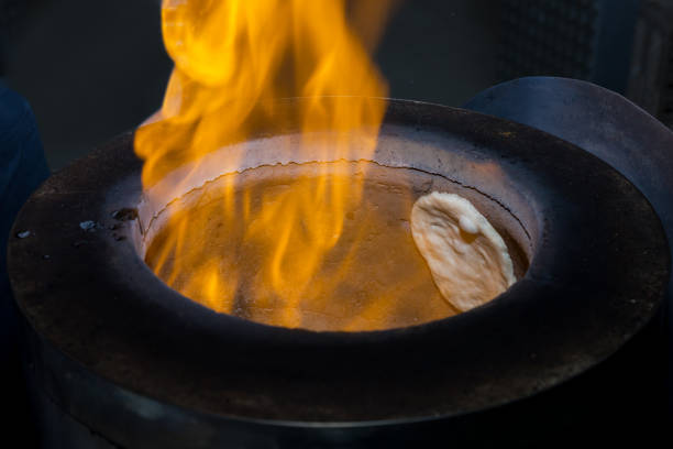 Making Naan Bread in a Tandoor Oven white plain raw naan bread in Tandoor oven with fire flame. naan bread stock pictures, royalty-free photos & images