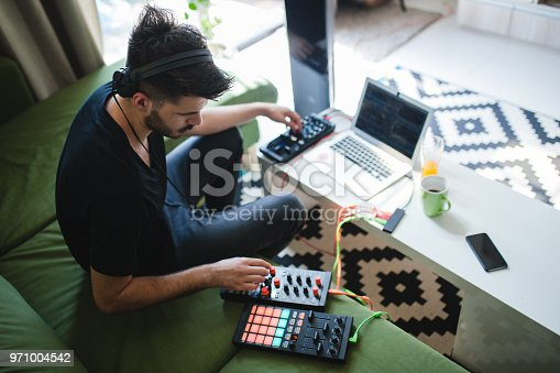 Young Man Enjoys Producing Music In Comfort Of living Room