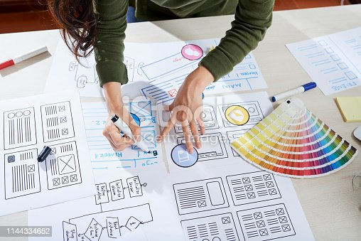 Directly above view of unrecognizable woman standing at desk and making notes on sketch of app interface while elaborating design