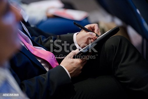 Business Man making notes at a conference seminar