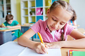 Education in school. Diligent little student with braids passing exam in the classroom. Girl learning new subject un school. She studying. It is perfect for using it in commercial and advertising photography, reports, books, presentation
