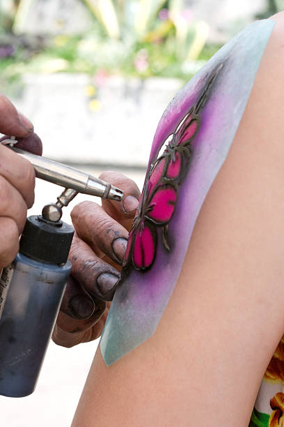 Making of a fake tattoo Artist brushing a tattoo. airbrush stock pictures, royalty-free photos & images