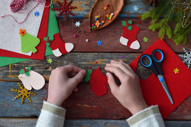 fabricación de juguetes de navidad hecha a mano de fieltro con sus propias manos. concepto de diy de los niños. hacer decoración de árbol de navidad o tarjetas de felicitación. paso 3. decorar el juguete - artesanía fotografías e imágenes de stock