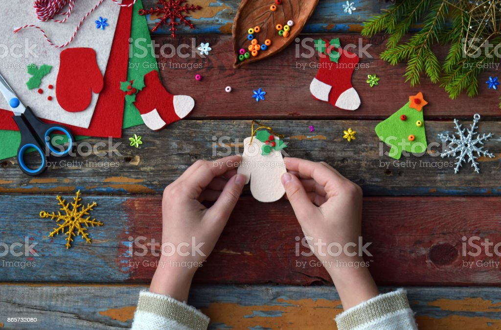 Making of handmade christmas toys from felt with your own hands. Children's DIY concept. Making xmas tree decoration or greeting card. stock photo