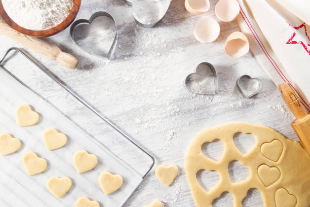 Making of Heart Shaped Cookies Making of heart shaped cookies with pastry dough and cookie cutter on white kitchen counter cookie cutter stock pictures, royalty-free photos & images