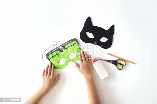 istock Making of masks from paper for the holiday Halloween from paper.  Frankinstein's  mask and Black cat. 849136388