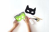 Making of masks from paper for the holiday Halloween from paper.  Frankinstein's  mask and Black cat.