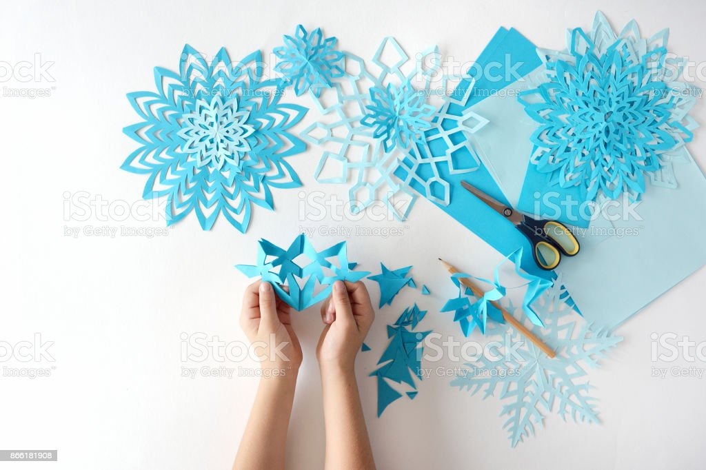 Making of snowflakes from blue paper. stock photo