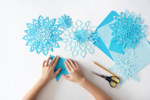 herstellung von schneeflocken aus papier. eine traditionelle weihnachts-kunsthandwerk-projekt - winterdeko basteln stock-fotos und bilder