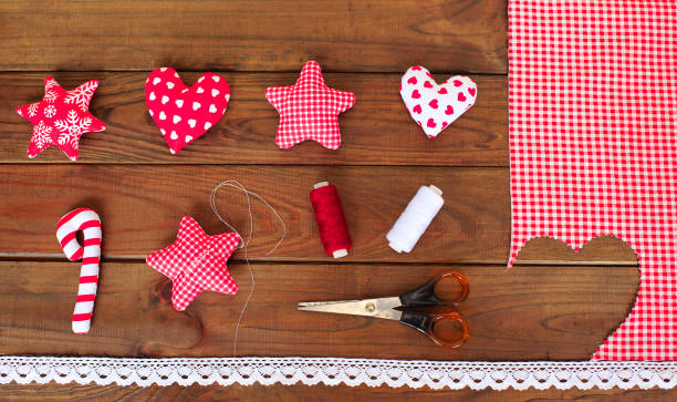 Making of textile handmade christmas toys on wooden background. Making xmas tree decoration or greeting card. Cut the toy. Easy Christmas crafts. stock photo