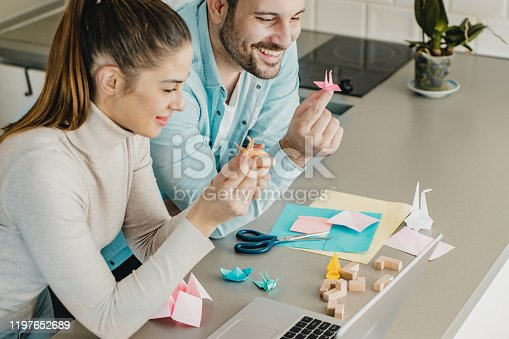 Young couple is at home using laptop and learning how to make origami