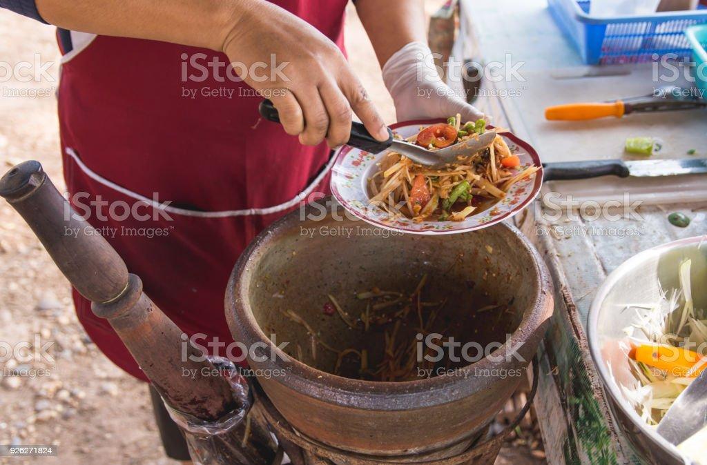 making papaya salad in a mortar, som tam, thai street food, stock photo
