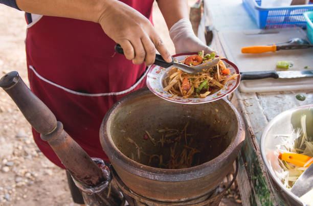 making papaya salad in a mortar, som tam, thai street food, stock photo
