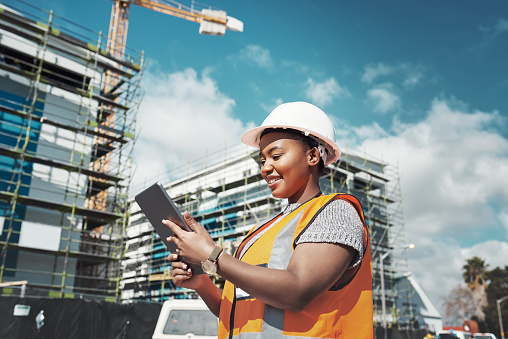 Shot of a young woman using a digital tablet while working at a construction site