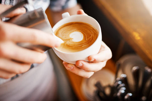 Making pictures A cropped shot of an unrecognizable barista pouring frothy milk into a cup of hot coffee turning it into a picture theobroma stock pictures, royalty-free photos & images