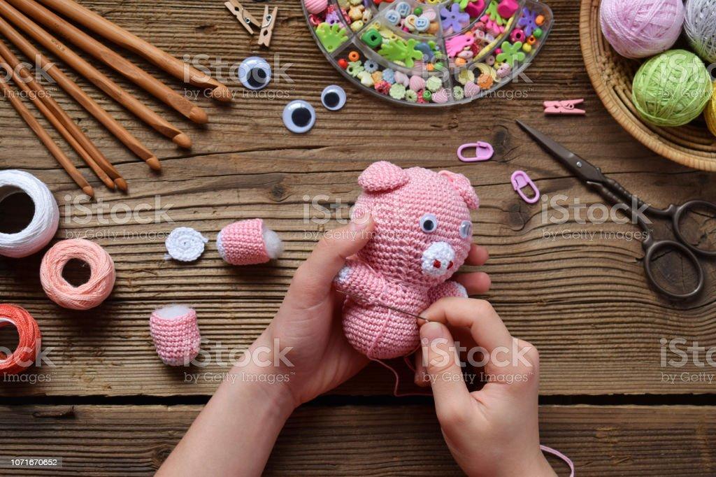 Haciendo el cerdo rosa. Crochet juguetes para el niño. En la tabla hilos, agujas, gancho, hilo de algodón. Paso 2: coser todos los detalles de juguete. Artesanías hechas a mano. Concepto de DIY. Pequeñas empresas. Ingresos de pasatiempo - foto de stock